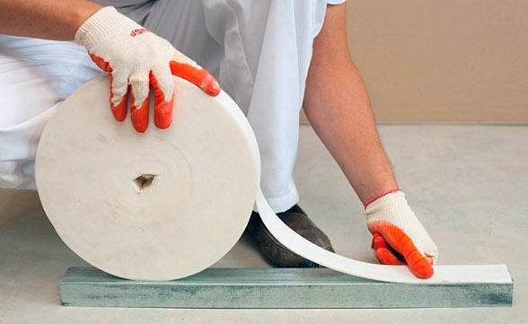 Уплотнительная лента – это пористый материал с самоклеющейся основой, шириной 30 мм. Её используют для крепления конструкции, чтобы каркас для потолка из гипсокартона плотно прилегал к бетону и меньше передавал звуки.