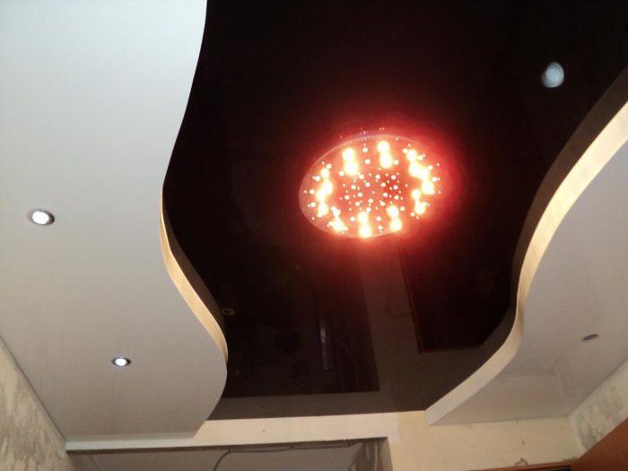 Двухуровневый натяжной потолок. Нижний уровень - белый глянцевый потолок со встроенными точечными светильниками, верхний - черный глянцевый с установкой люстры на платформу