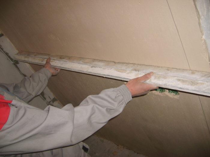 Выравнивание стен шпаклевкой. Разводится сухая смесь водой, в соответствии с инструкцией на упаковке. Затем набирая немного замазки на шпатель, заполняйте ею все выемки, какие увидите. Для идеальной поверхности шпатлевку наносят на всю поверхность. Последний слой выравнивают широким шпателем, ведя им вдоль всей длины стены.
