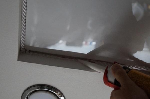 Наносим герметик под основание планки, куда заправляется потолок. Начинаем наносить с одного из углов, если они есть.