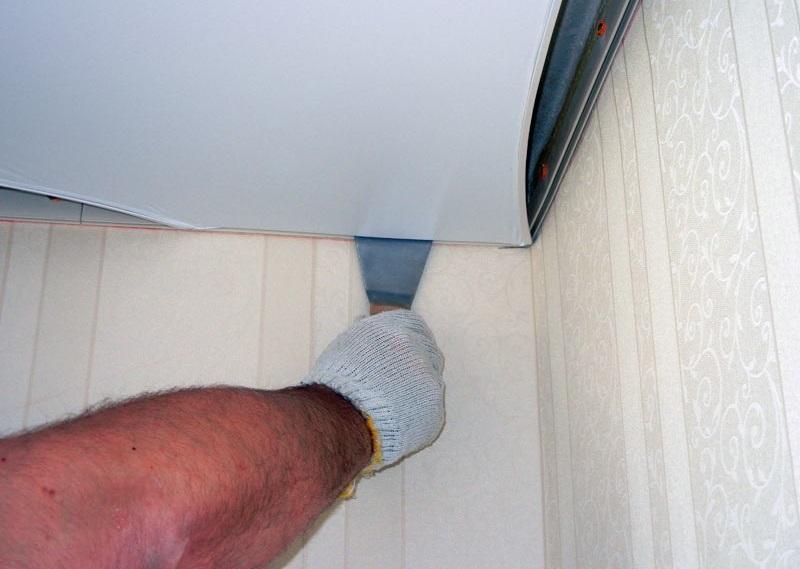 Закрепляется первый угол полотна натяжного потолка: гарпун (окантовка) заправляется шпателем в багет