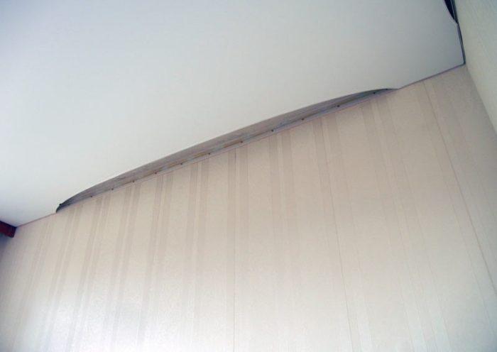 И последовательно закрепляем углы натяжного потолка в багете