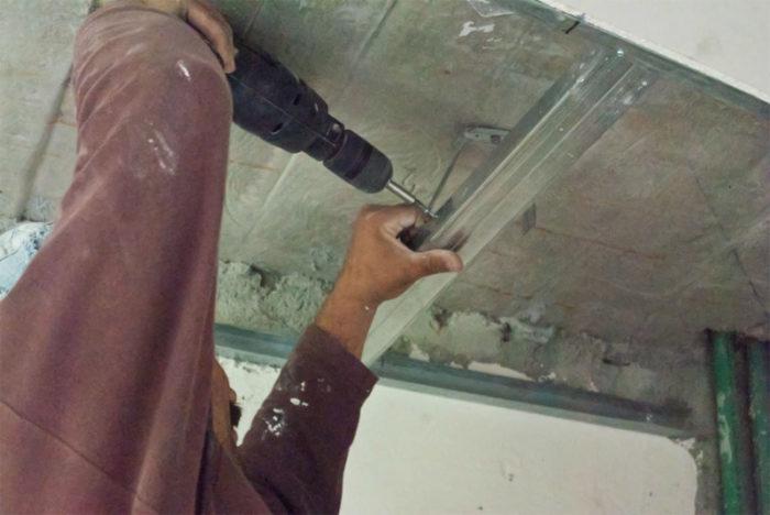 Крепление поперечного потолочного профиля при помощи подвеса