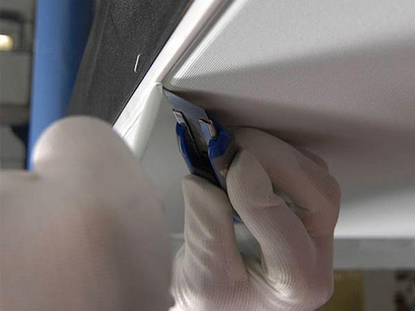Обрезаются излишки полотна при монтаже тканевого натяжного потолка