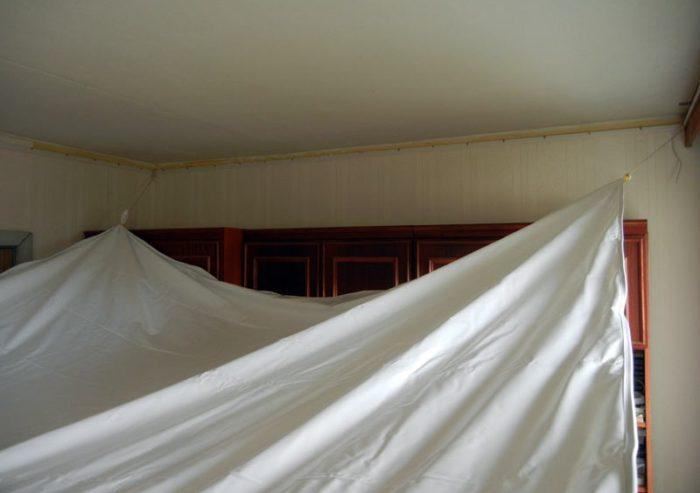 Пока полотно натяжного потолка не прогрето - оно провисает и напоминает по виду большую простыню