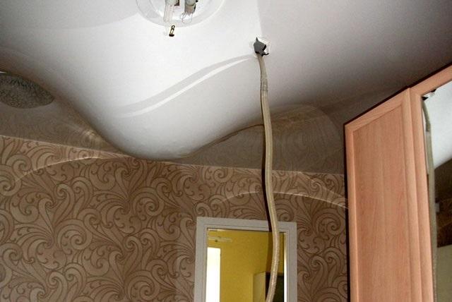 Слив воды с натяжного потолка при помощи шланга