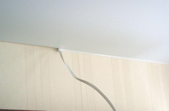 Стык между полотном натяжного потолока и стеной декорируют гибким ПВХ лентой - галтелью