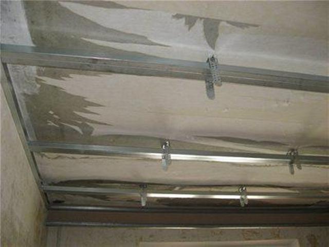 Каркас гипсокартонного потолка: основные профили вставлены в направляющие и подсоединены к подвесам